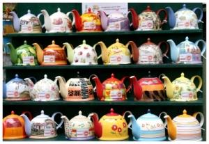Bunte Teekannen in vier Reihen übereinander im Regal